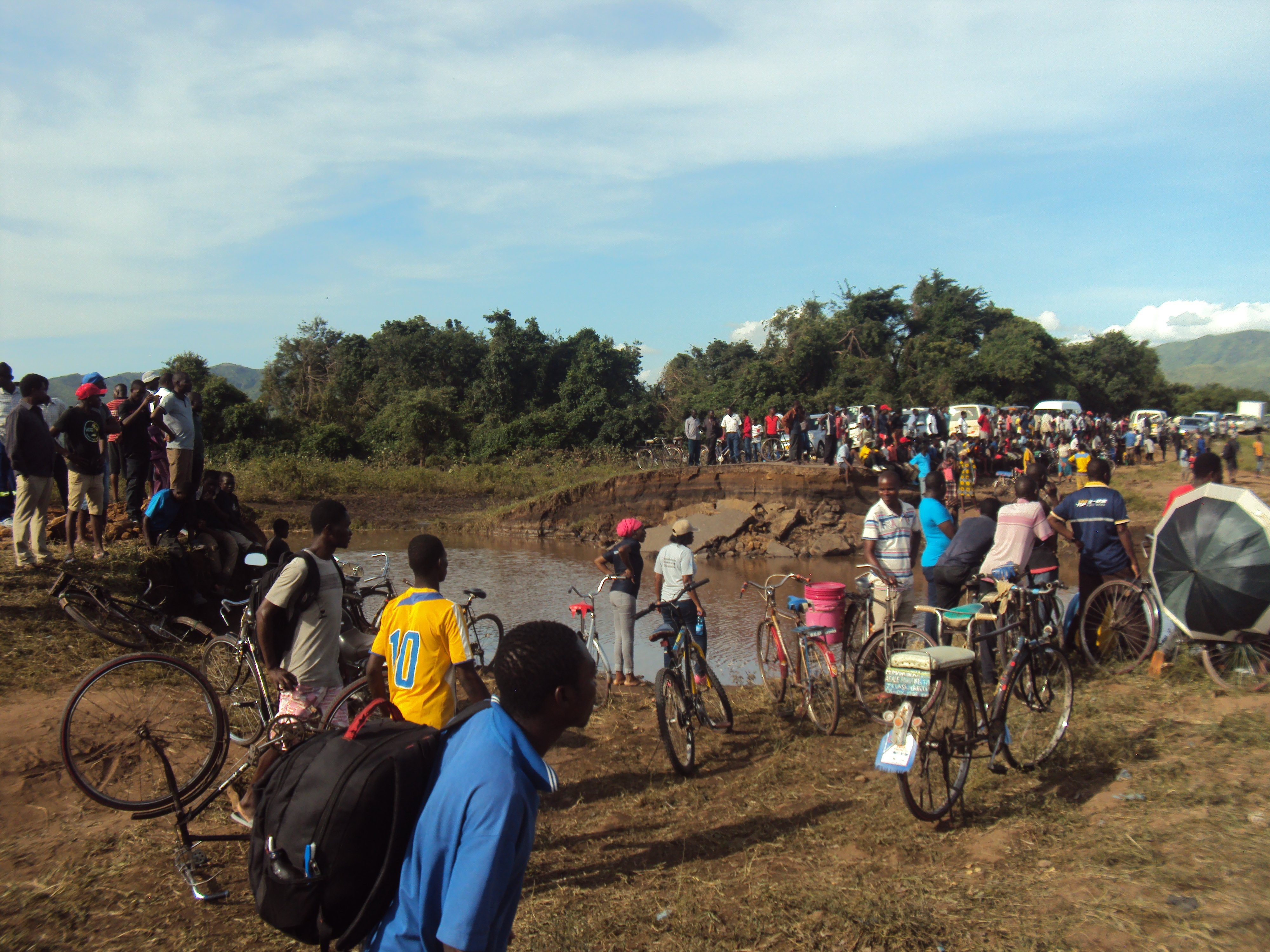 Crowd of people pushing bicycles and carrying goods across a muddy landscape