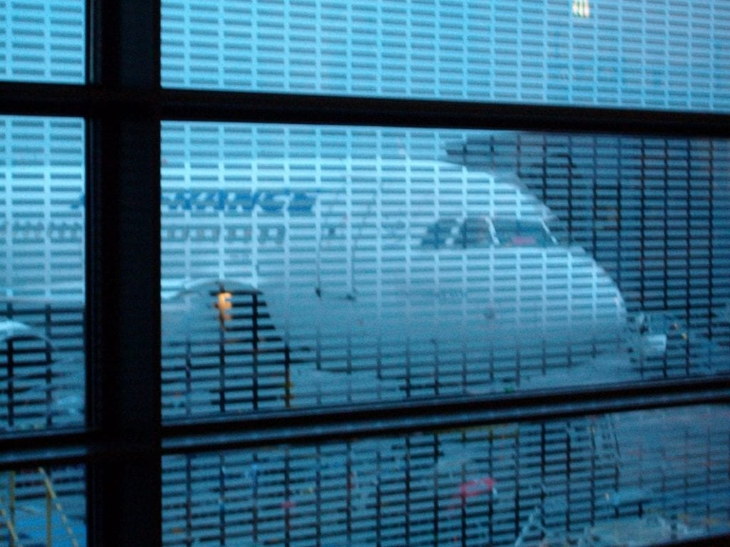 Aeroplane seen through an airport window. Aeroplane travel is far from carbon neutral.